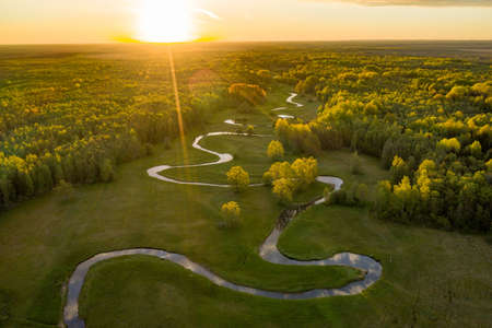 Forest in summer colors. Green deciduous trees and winding blue river in sunset. Mulgi meadow, Estonia, Europe 版權商用圖片