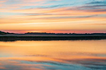 Evening sunlight on coast, pink clouds, blue sky reflection on water. Beach in summer. Seaside natural environment. Shore in Laelatu, small island in Estonia. Nature Reserve in North Europe