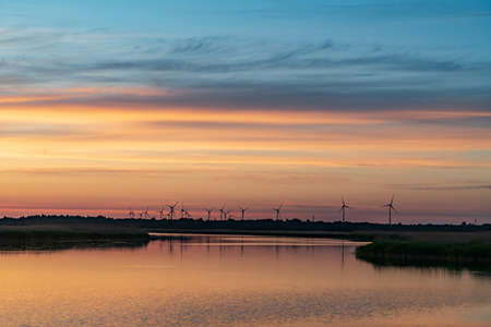Evening sunlight on coast, pink and golden clouds and wind turbine. Sky reflection on water.  Wind generator for electricity, alternative energy source. Windmill for electric power production.