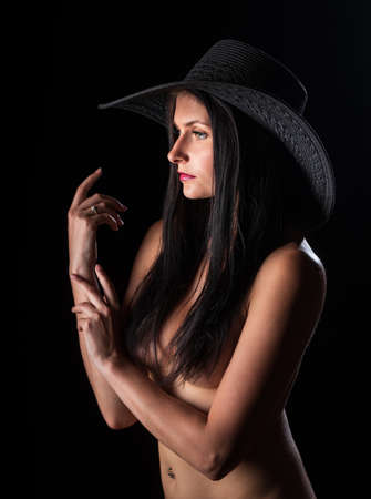 Young nude woman with make up. Model with hat. Naked girl beauty portrait on black background.