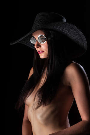 Young nude woman with make up. Model with glasses. Naked girl beauty portrait on black background. Standard-Bild