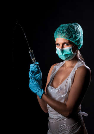 Sexy doctor in medical mask make protective injection. Naked nurse prepares syringe. Medic in disposable medical clothing. preparing vaccination against for a pandemic and flu season.