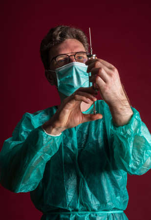 Doctor in medical mask make protective injection. Nurse in glasses prepare syringe. Medic preparing vaccination against for a pandemic and flu season. Dentist in disposable medical clothing.