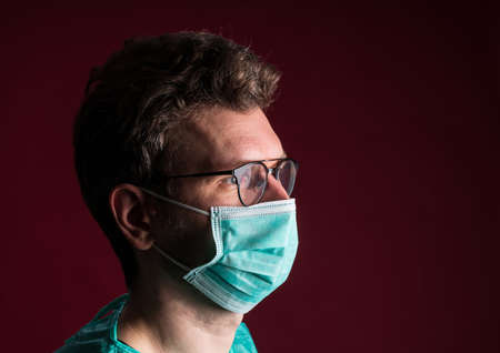 Doctor in protective medical mask. Nurse in glasses prepare for surgery. Medic disposable medical clothing against for a pandemic and flu season.