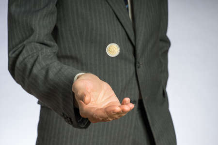 Business man with gray jacket throws up a euro coin. European finance currency.