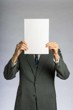 Businessman holding a white paper in front of his head. Blank sheet and man in suit.
