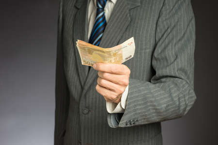 Businessman hand holding money, euro bills. Banknotes isolated gray background. Hand holding out a stack of fifty euros