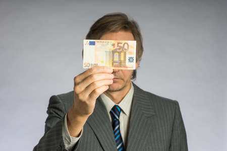 Businessman hand holding money, euro bill. Hands holding fifty euros in front of face Standard-Bild