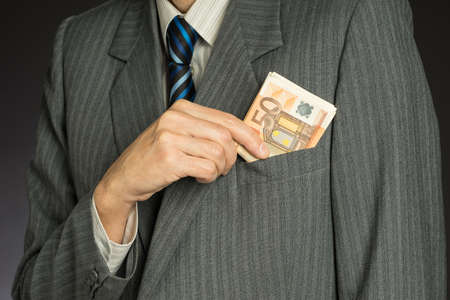 Businessman in suit putting banknotes in his jacket breast pocket. Business man is holding cash, stack of fifty euros money. Person pays in euro bills, isolated gray background. Standard-Bild