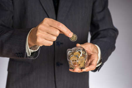 Business man with gray jacket putting euro coin  into the  piggi bank. European finance currency. Guy holding money box Standard-Bild
