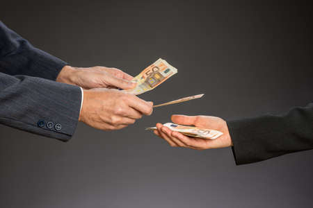 Deal! Businessman paying money  (fifty euros) to businesswoman. Woman and man hand on a gray background.  Standard-Bild