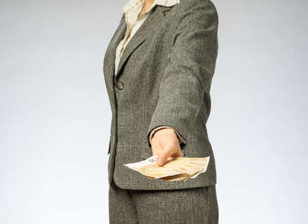 Business woman with gray jacket parses the money fan. European finance currency, fifty euro banknotes