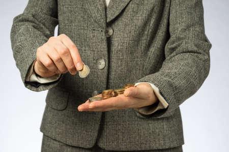Business woman holding money in hand. European finance currency, coins. Standard-Bild