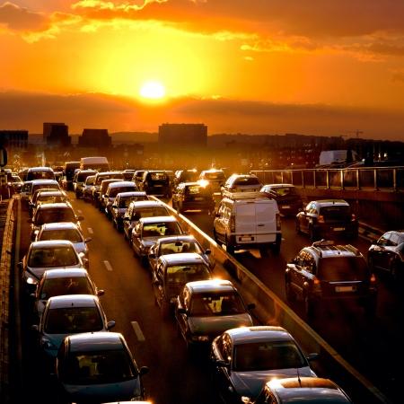 Avond verkeer. De stadslichten. Het autoverkeer tegen de zonsondergang achtergrond. Stockfoto