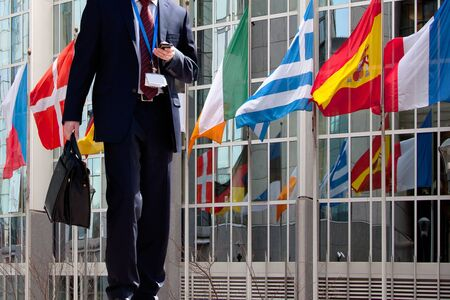 european parliament: Functionary calling on the phone. Flags of Europe. Businessman. Stock Photo