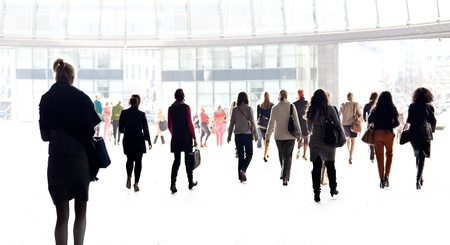 Silhouettes of people against the light background. A large group of people. Stock Photo