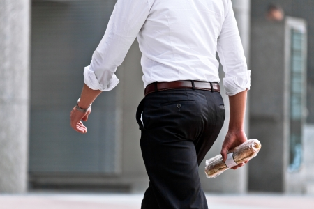 Walking man with a sandwich. Urban scene.