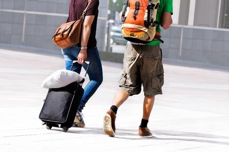 mochila viaje: Pareja joven con una bolsa de viaje. Escena urbana.