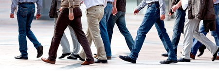 Group employees going against the office. Panorama. A group of businessmen. Stock Photo