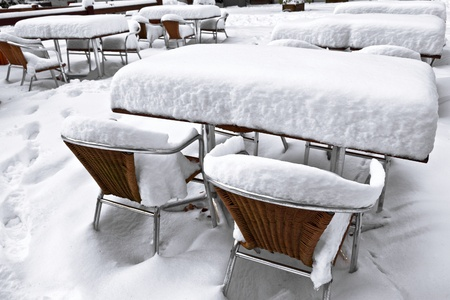 Cafe with snow  Winter landscaper  Garden furniture melting after a snowstorm  photo