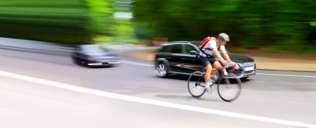 Blurred motion. Cyclist and car on the highway. Abstract background. photo