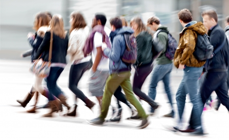 walking: A large group of young people. Urban scene.