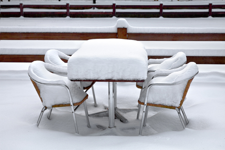 Cafe with snow. Winte landscaper. Garden furniture melting after a snowstorm. photo