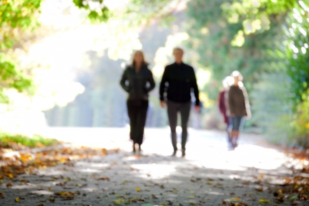 serene people: People in the autumn park. Blurred motion.