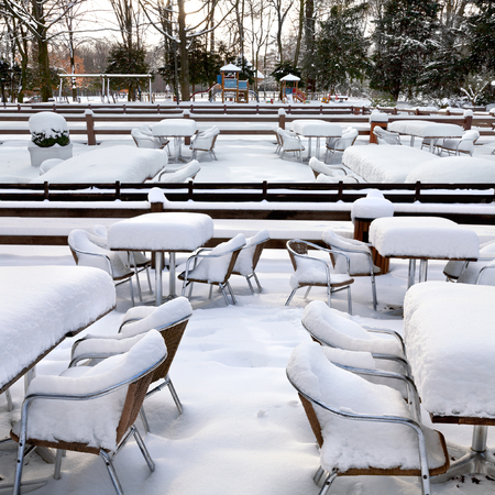 Cafe with snow. Winter landscaper. Garden furniture melting after a snowstorm. photo