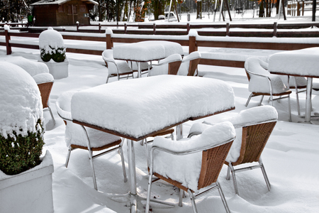 Cafe chairs in Park. Bistro Set Melting. Garden furniture melting after a snowstorm. photo