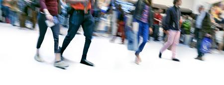 personnes qui marchent: Un grand groupe de personnes marchant. Flou de mouvement. Panorama.