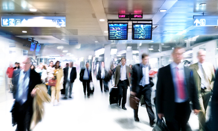 hall: A large group of arriving businessmen. Panorama. Motin blur.
