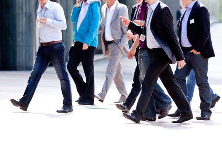 Businessmen walking on the street. Urban scene. photo