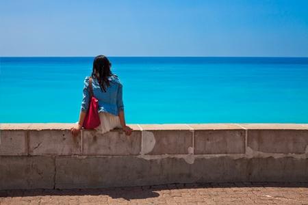 Nadenkend meisje op het strand. Zeegezicht.