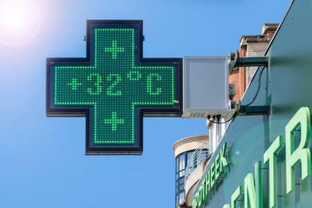 Thermometer in green pharmacy screen sign displays extremely hot temperature of 32 degrees Celsius during heatwave  heat wave in summer in Belgium 스톡 콘텐츠