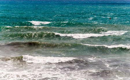 Blue and green waves breaking ashore mid July 2012 at Cala Capitan, La Zenia, Spanish Mediterranean coast   photo