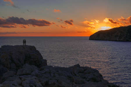 Romantic couple on a rock by the Mediterranean ocean at a sunset in February  photo