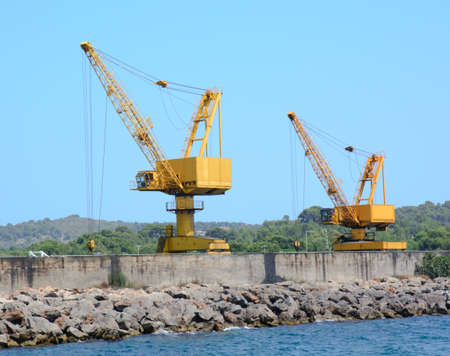 Two yellow industrial cranes on a jetty photo
