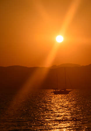 Sailboat with two masts at sunset in golden light  photo