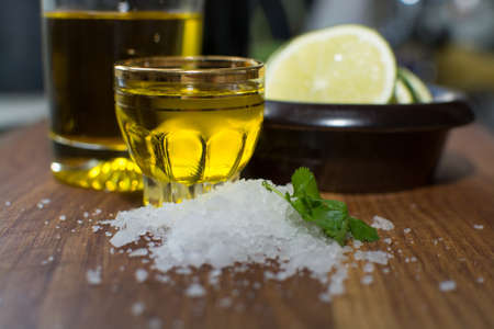 stoneware: Heap of sea salt, coriander, olive oil in a small shot glass and slices of lime in a small dark brown stoneware bowl on oak  Stock Photo
