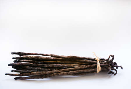 Vanilla pods with straw bow isolated on white