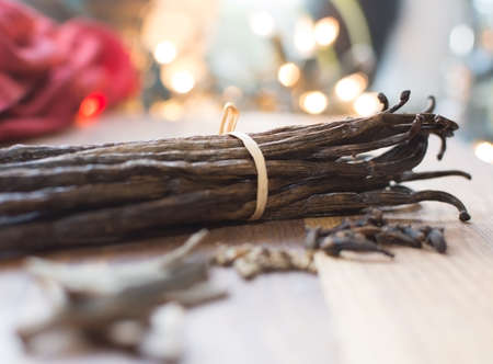 Vanilla pods with spices like cardamom, cinnamon and gleaming holiday lights  Stock Photo