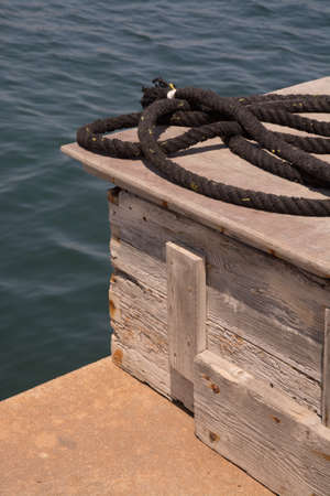 Mooring rope on a wood box on a jetty. photo