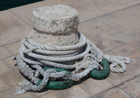 White mooring knob with ropes and green rubber. photo