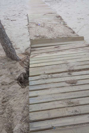 Deep erosion in the sand and broken boardwalk in Camp de Mar, Andratx, Majorca, the day after the big storm of October 29 2013 Stock Photo - 24327854