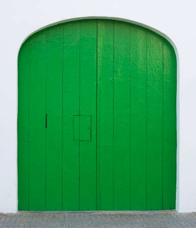 whitewashed: Green painted door with hatch and rounded top on whitewashed wall, Majorca, Spain  Stock Photo