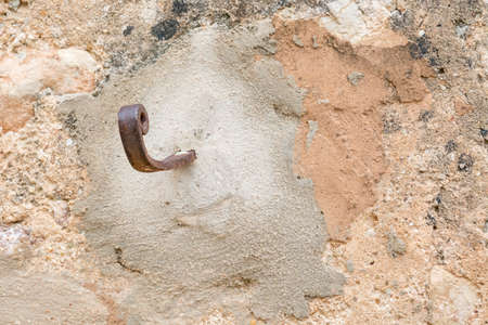 Rusty hook to the right on plastered wall with grungy look and warm earthy colors Stock Photo - 24480820