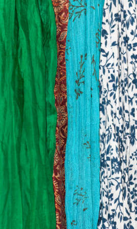 gauzy: Fabrics vertical. Assortment of fabrics in organic theme - green silk, red indian wool, turquoise gauzy cotton and white cotton with marine blue floral.