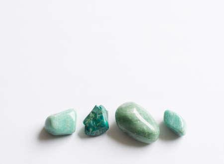 Vier groene halfedelstenen. Turquoise, Aventurijn, amazonite op een witte achtergrond.