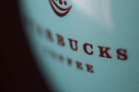 starbucks: Abstract extreme closeup of Starbucks coffee mug in turquoise color with brown text.